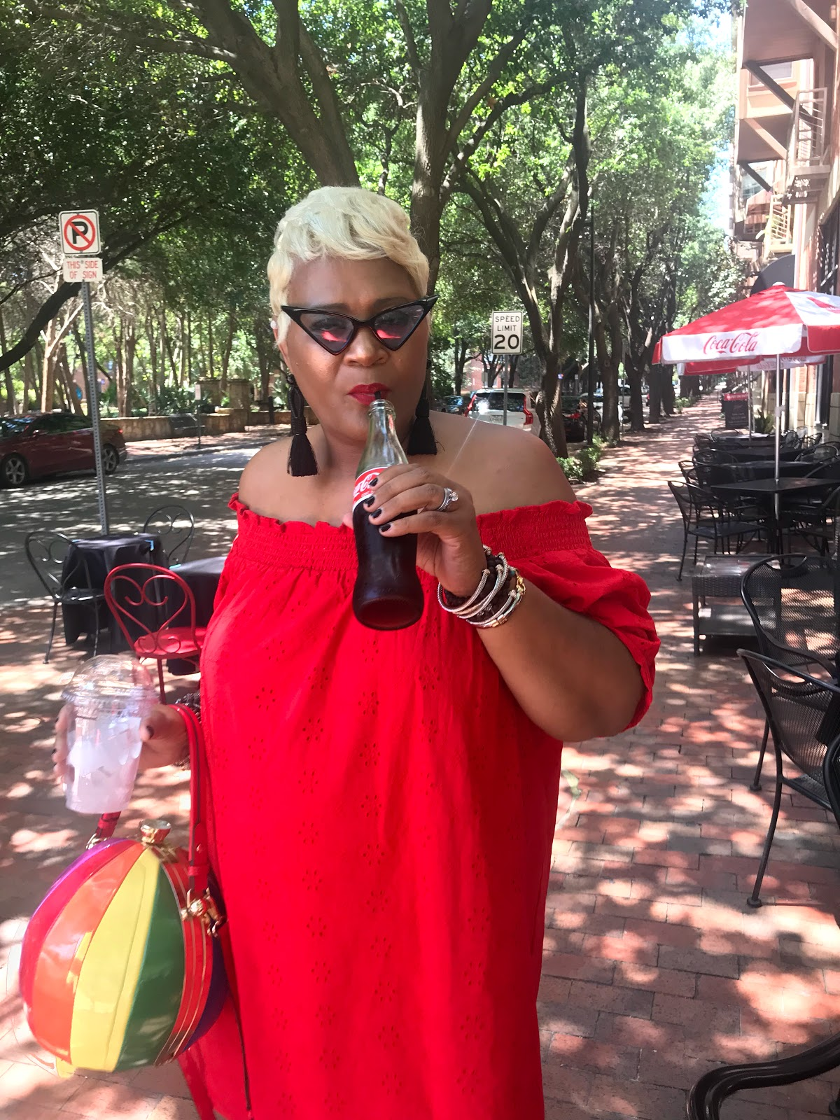 Image: Tangie Bell wearing red dress and drinking a cola in the sun. Sharing her choldhood stories about the heat and Cooter Brown. Seen first on Bits and Babbles Blog