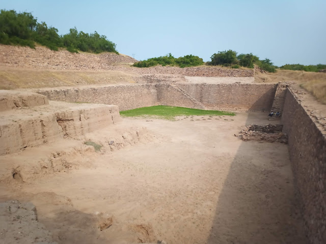 Empty reservoir cut into ground with stairs leading into it at Dholavira