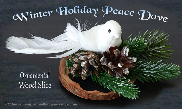Annie Lang's winter holiday peace dove craft sits on top an evergreen branch, pine cones and a wood slice round disc base.