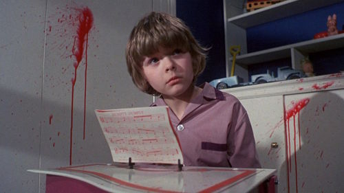 Small boy sitting down with blood on the wall behind him