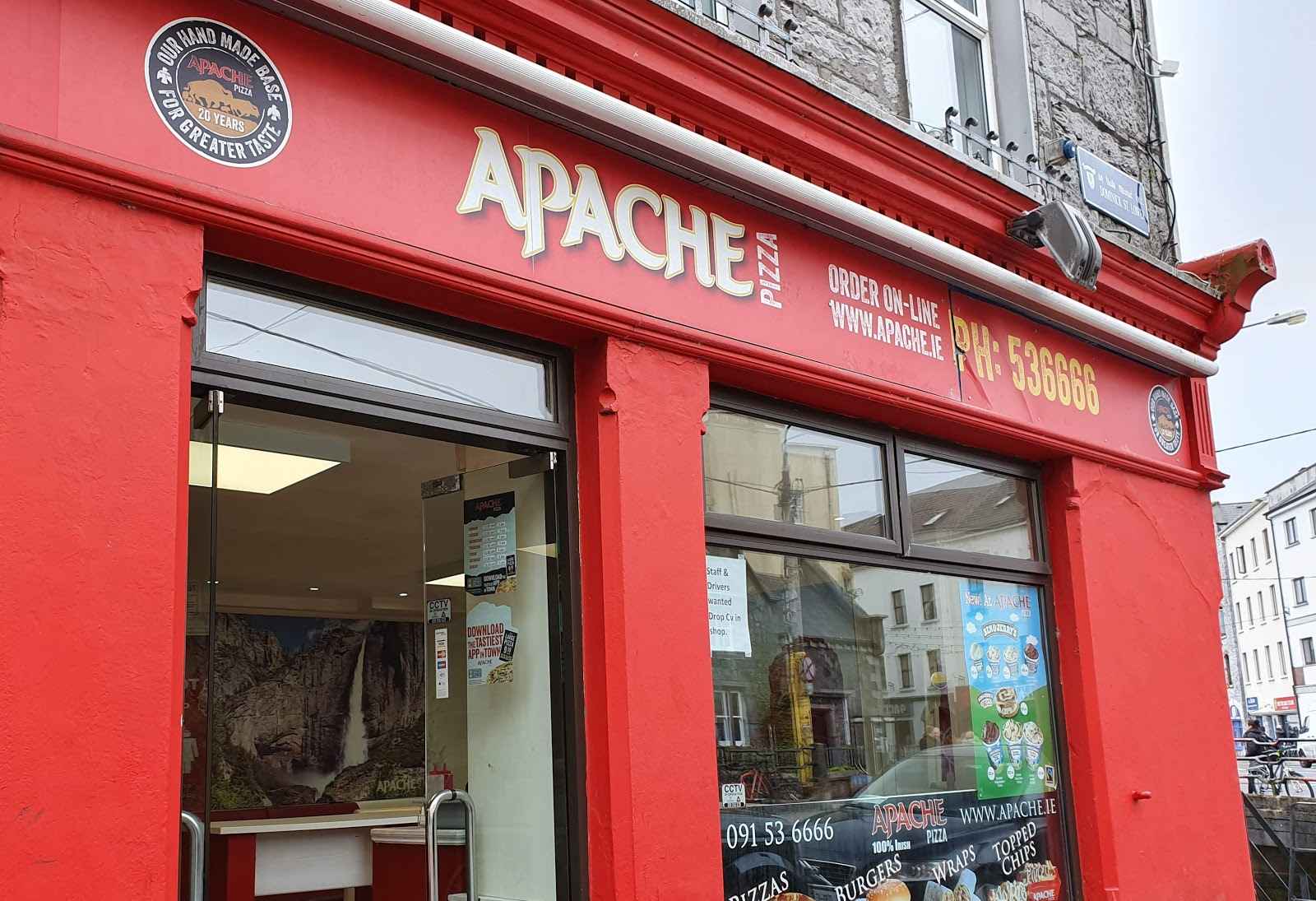 Shop doorway and front window with sign.  Apache Galway phone 091 536 666 - Apache Pizza 20 years our hand made base for better taste - circular logo with buffalo silhouette figures inside