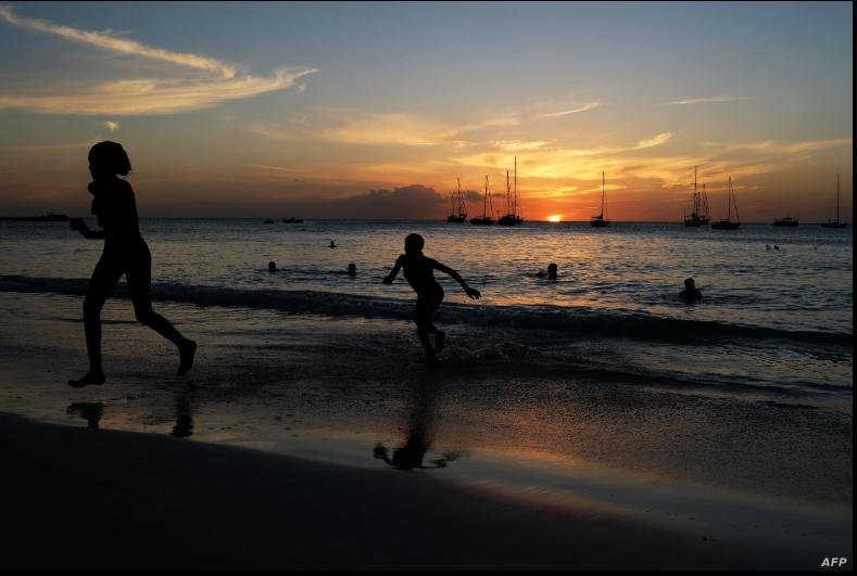 Turistas en una playa de Bridgetown, Barbados, en el atardecer del 24 de marzo de 2017. Barbados ha anunciado su intención de convertirse en república en noviembre de 2021 / AFP