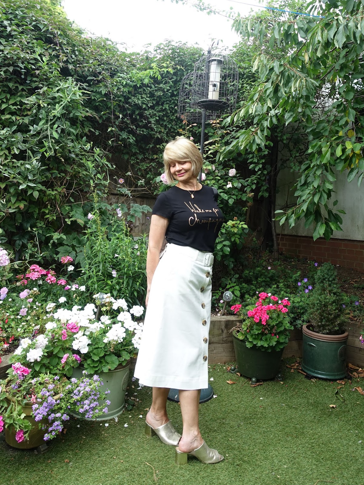 Posing in the summer garden Is This Mutton style blogger Gail Hanlon wearing gold mules, a black slogan tee and white midi A line skirt