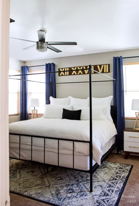 Modern white black indigo blue master bedroom with roman numeral wall art