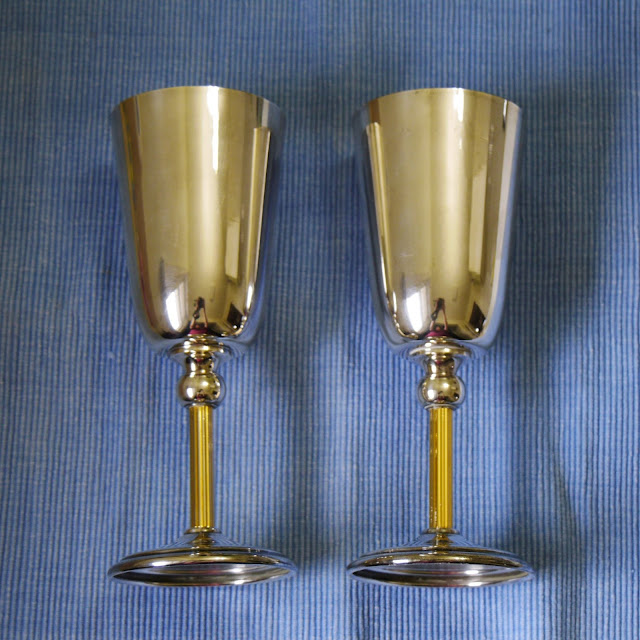 Two freshly polished shiny silver cups lay next to each other on a blue placemat.