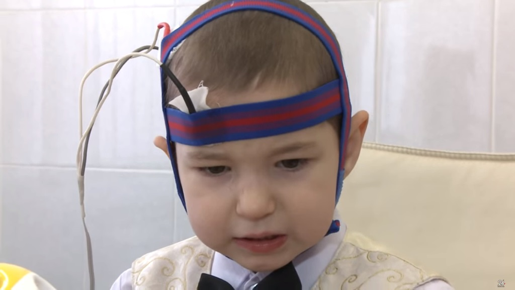 ребенок во время микрополяризации: на голове резинка с установленными электродами