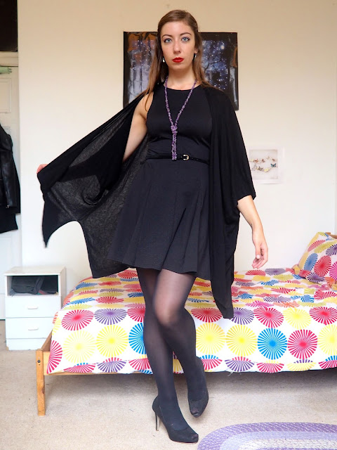 Maleficent inspired Disneybound outfit of little black dress with cape cardigan, tights & high heels, and green & purple jewellery