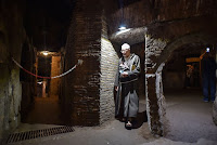 "A friar walks towards the restored ""dei Fornai"" (bakers) cubicle, during a visit after the restoration of the catacomb of Santa Domitilla, in central Rome, on May 30, 2017 [Credit: AFP/Andreas Solaro]"