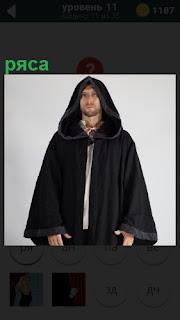 В черной рясе с капюшоном стоит священник и молча смотрит