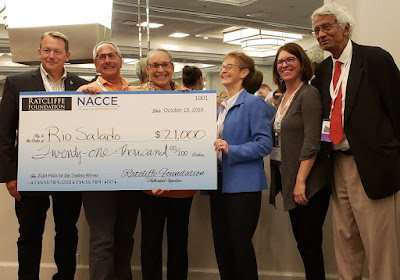 photo shows contest winner holding $21,000 check with 5 other people in the photo