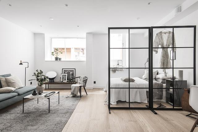 Paravan de sticlă, living și dormitor în aceeași cameră într-o garsonieră de 50 m²