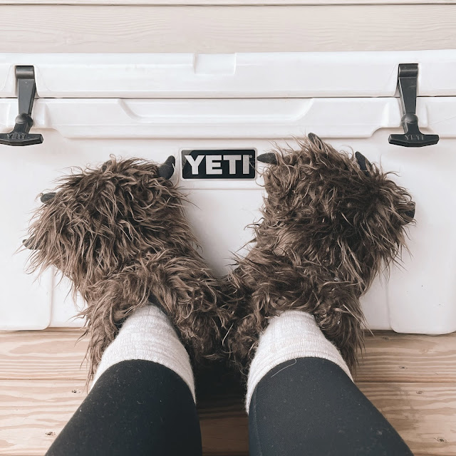 giant brown fuzzy slippers against an ice chest