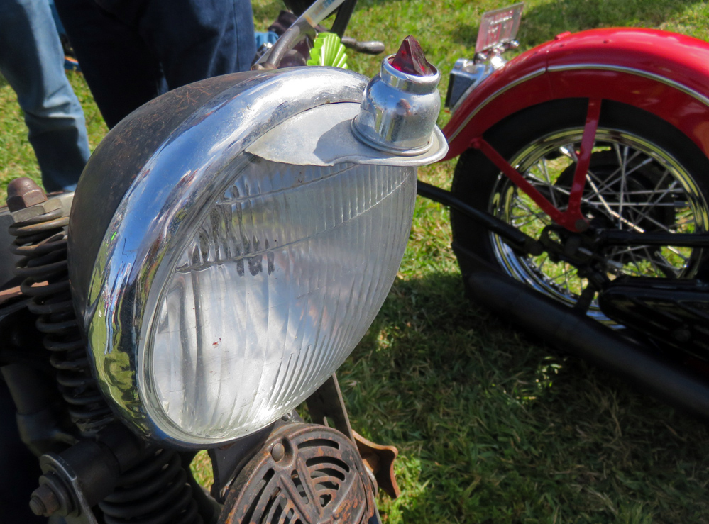 Headlight has hood with a ruby plastic piece.