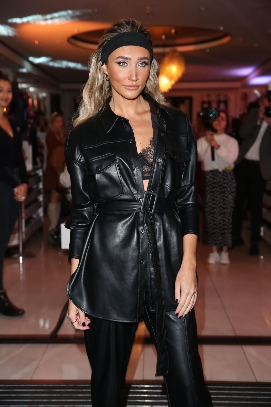 Megan McKenna flashes her lace bra in a black leather shirt and cigarette trousers as she leads the stars at her lingerie launch bash