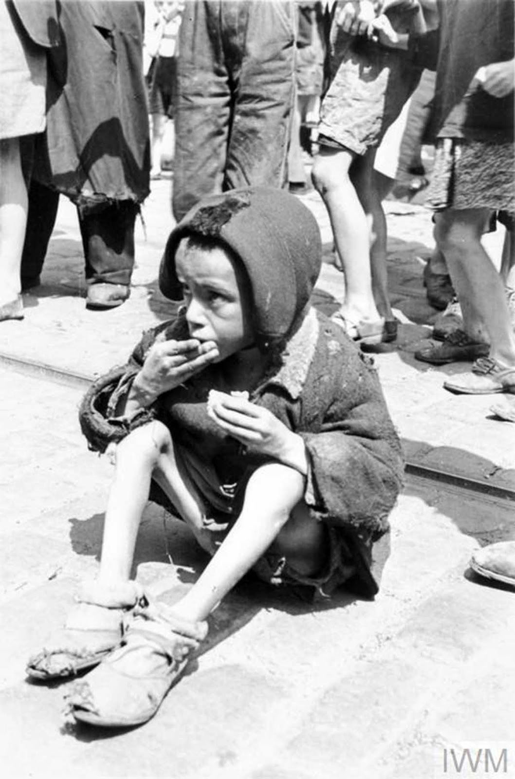 A destitute Jewish child eating a piece of bread in the street of the ghetto.