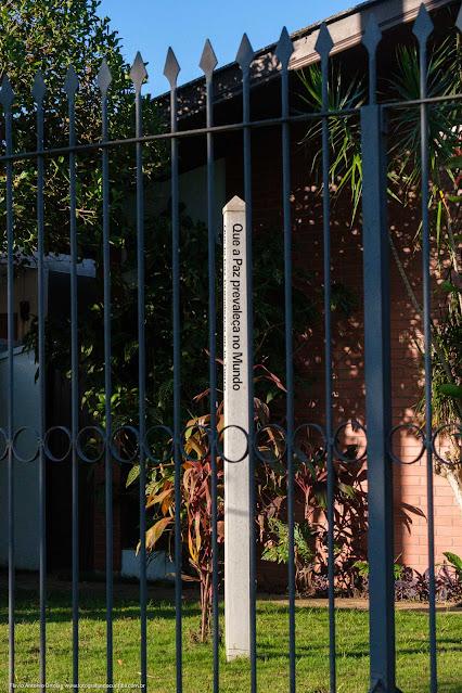 """Postinho no jardim de uma casa com a frase """"Que a Paz prevaleça no Mundo"""""""