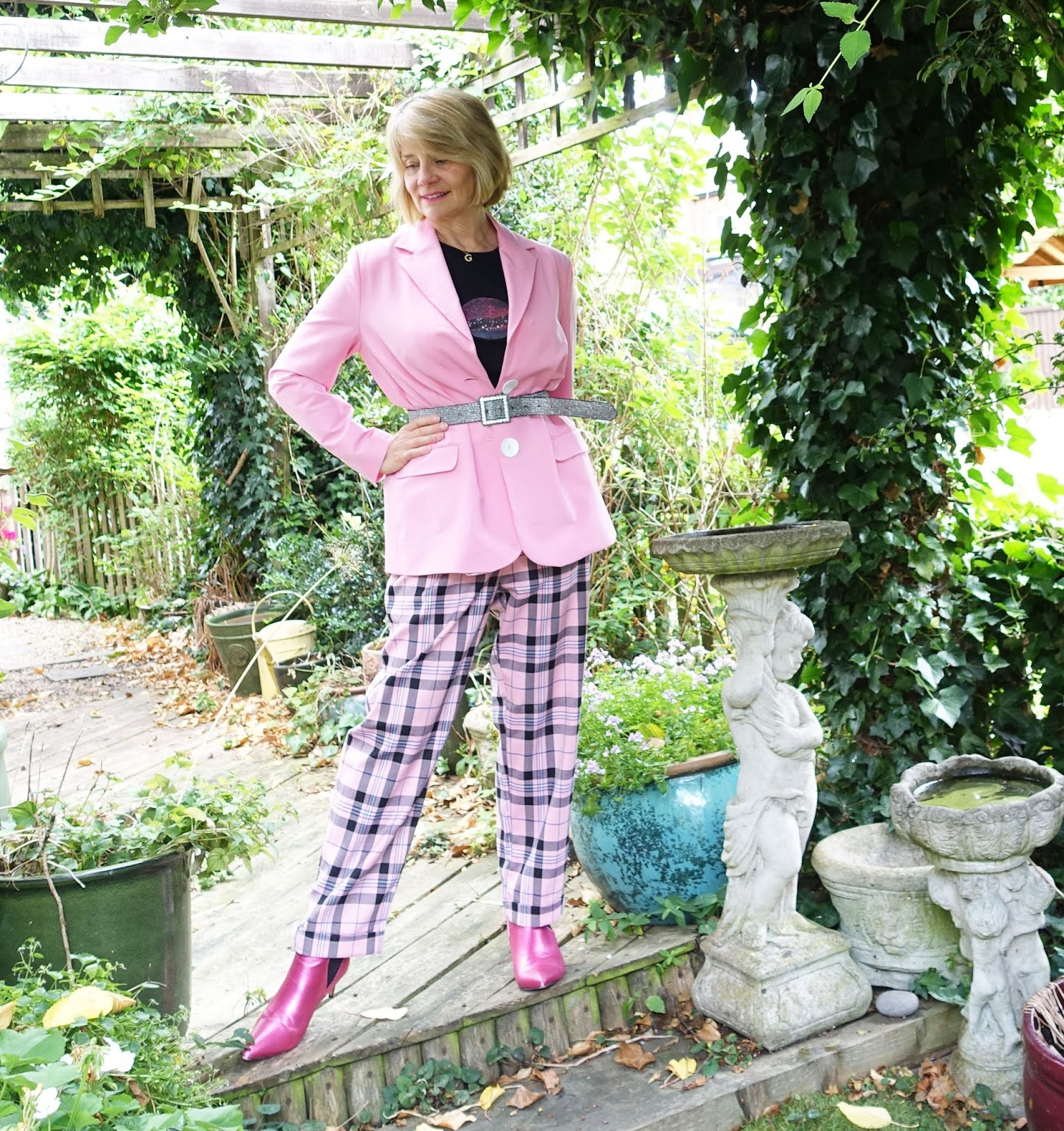 Over-50s blogger Gail Hanlon from Is This Mutton in pink and black with check trousers, belted jacket and bright pink ankle boots for the Check Me Out Challenge