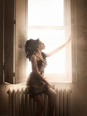 Amy Winehouse sitting in a window with light surrounding her