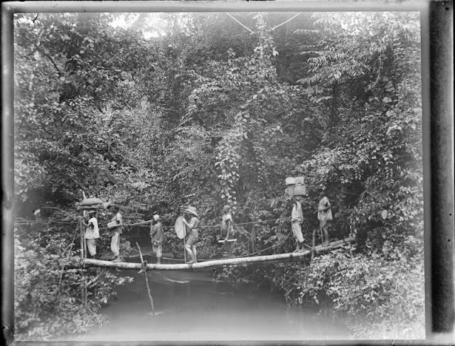 Crossing a river by precarious footbridge. E.O. Teale Collection