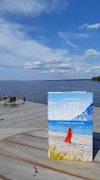 Kirja puisella terassipöydällä, taustalla iso terassi ja sen takana suuri järvi