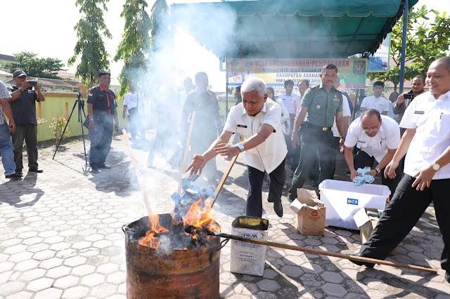 Wakil Bupati Asahan Surya memasukkan e-KTP ke dalam tong untuk dibakar.