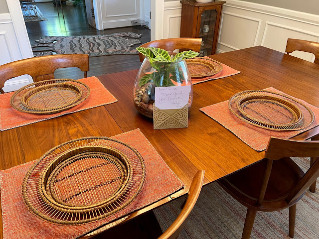 dining table with placemats and terrarium