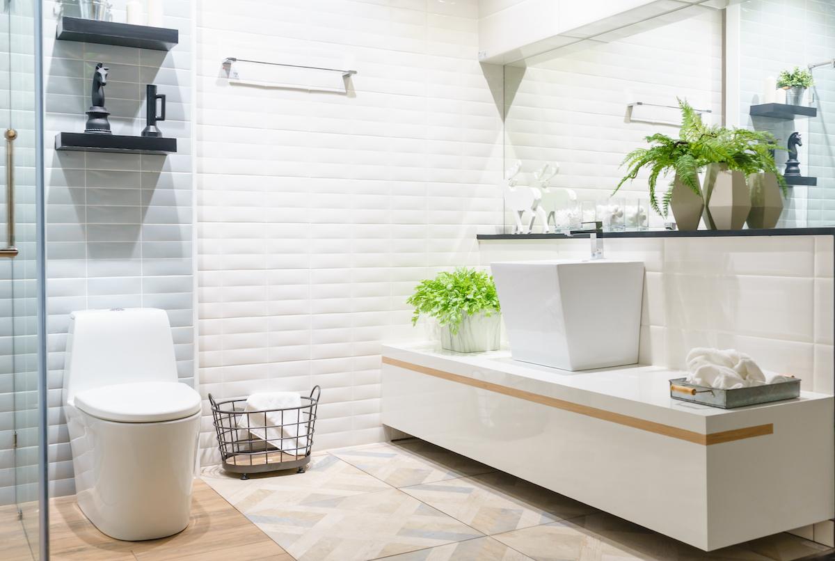Baño en blanco y azul con suelo porcelánico imitación madera