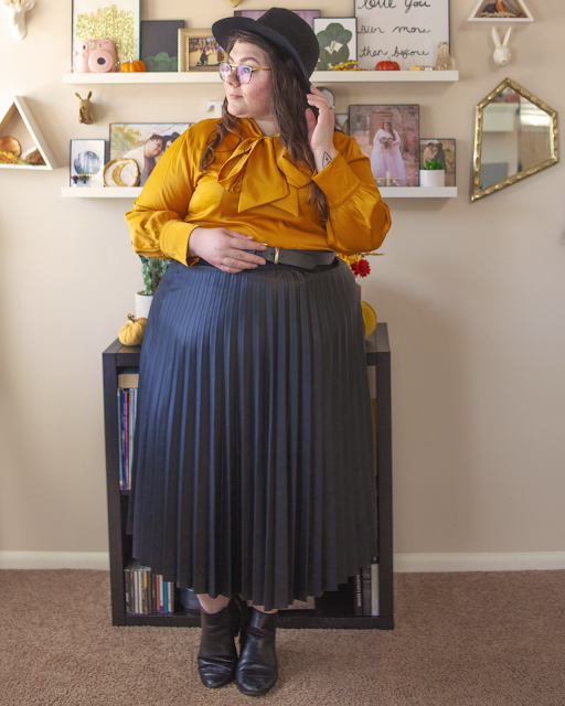 An outfit consisting of a wide brim black fedora, a mustard yellow long sleeve silk blouse with an attached pussy bow, tucked into a black faux leather pleated midi skirt and black Chelsea boots.