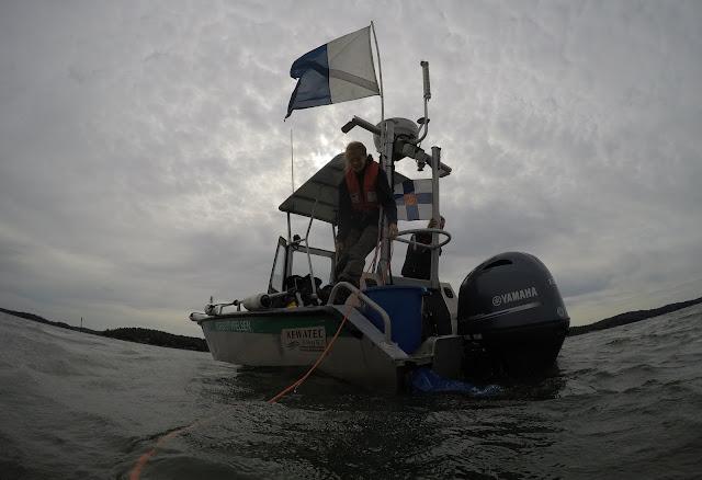 Vene ja kaksivärinen sukelluslippu vedestä katsottuna