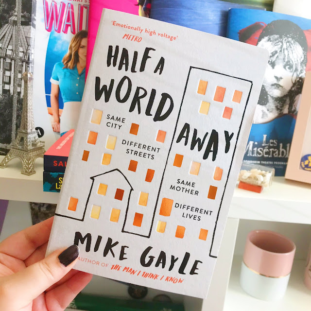 Half A World Away by Mike Gayle book held up in front of desk