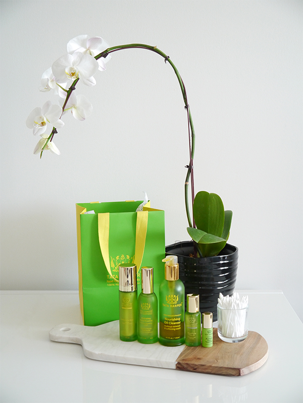 Tata Harper products displayed on a marble board, in front of an orchid, on a white table