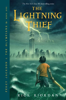 A boy (Percy) stands in water during a storm in front of a city skyline, holding a sword and a horn