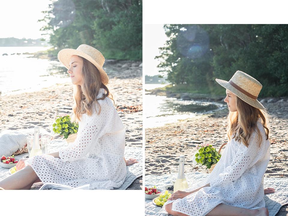 Woman on a beach picnic wearing a white dress and straw hat - Nainen piknikillä rannalla, valkoinen mekko ja olkihattu