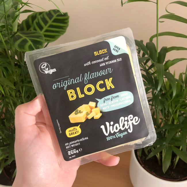 hOLDING A VIOLIFE BLOCK OF VEGAN CHEESE IN FRONT OF GREEN HOUSEPLANTS