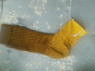 A gradient sock running from brown at the cuffs to yellow along the heel.  The foot is incomplete and still live on the needle.  There are slipped stitches spiralling along the leg of the sock and the top of the foot.