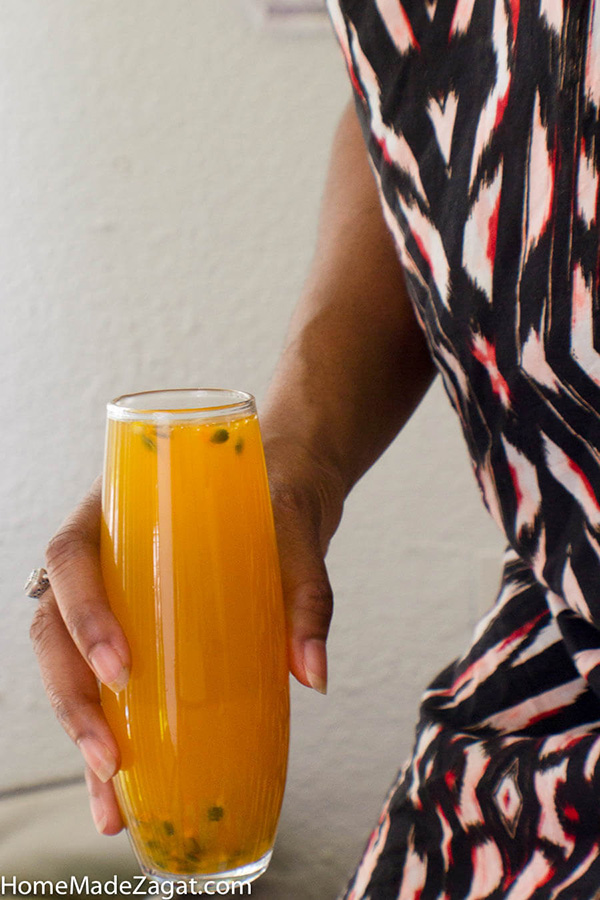 Hand holding a glass of mango passion fruit juice