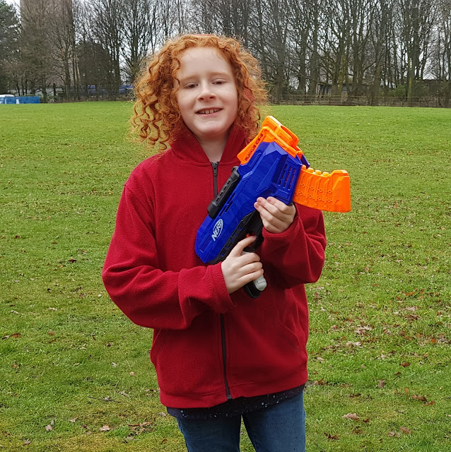 Boy holding Nerf Rukkus ICS-8 Nerf N-Strike Elite on parkland
