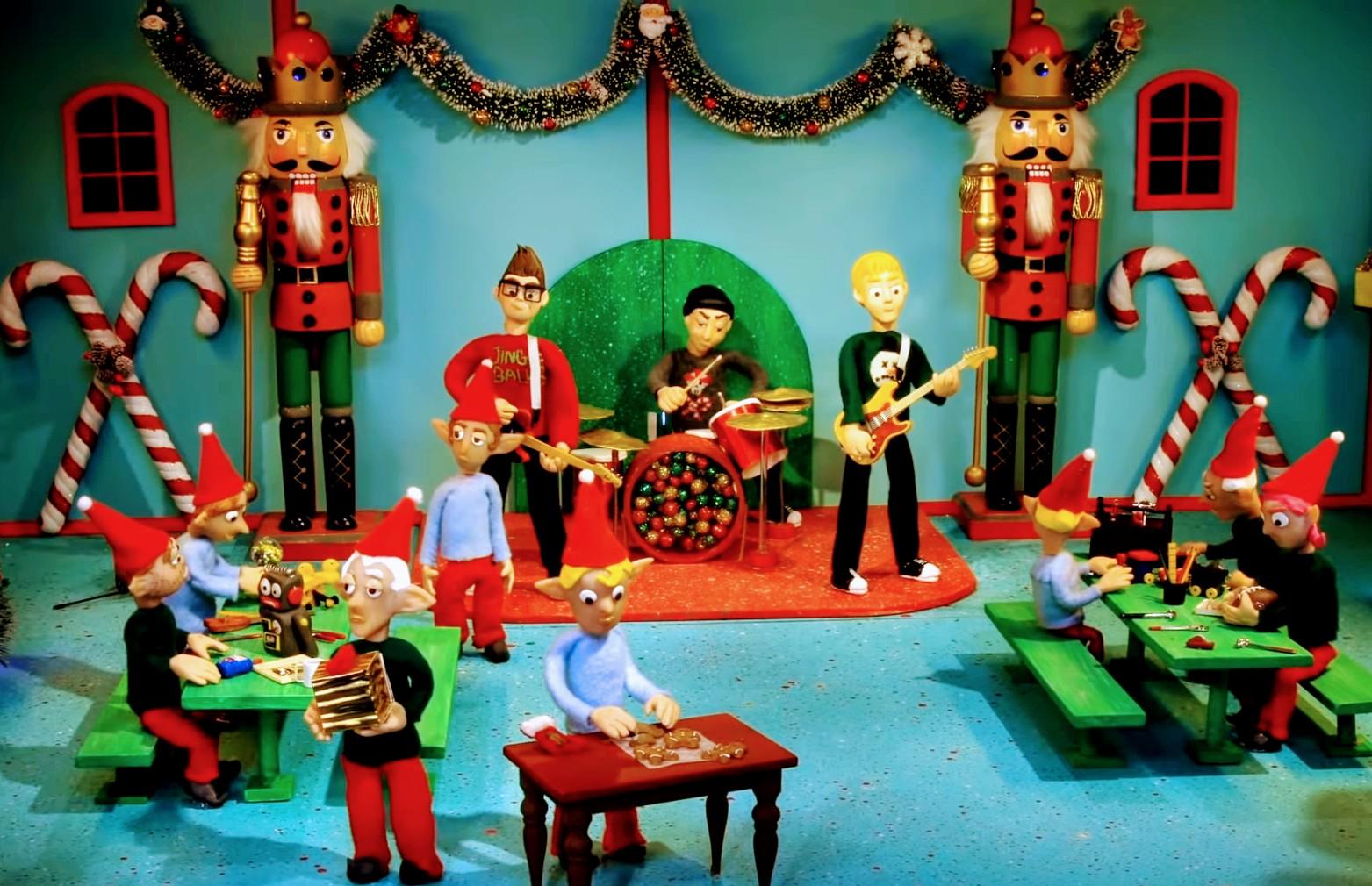Imagem retirada do clipe do YouTube: A banda Blink-182 representada em bonecos de massinha, que estão tocando a música dentro da fábrica do Papai Noel, em meio a enfeites de natal e duendes.