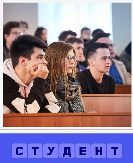 в зале сидят студенты на лекции за столами и слушают