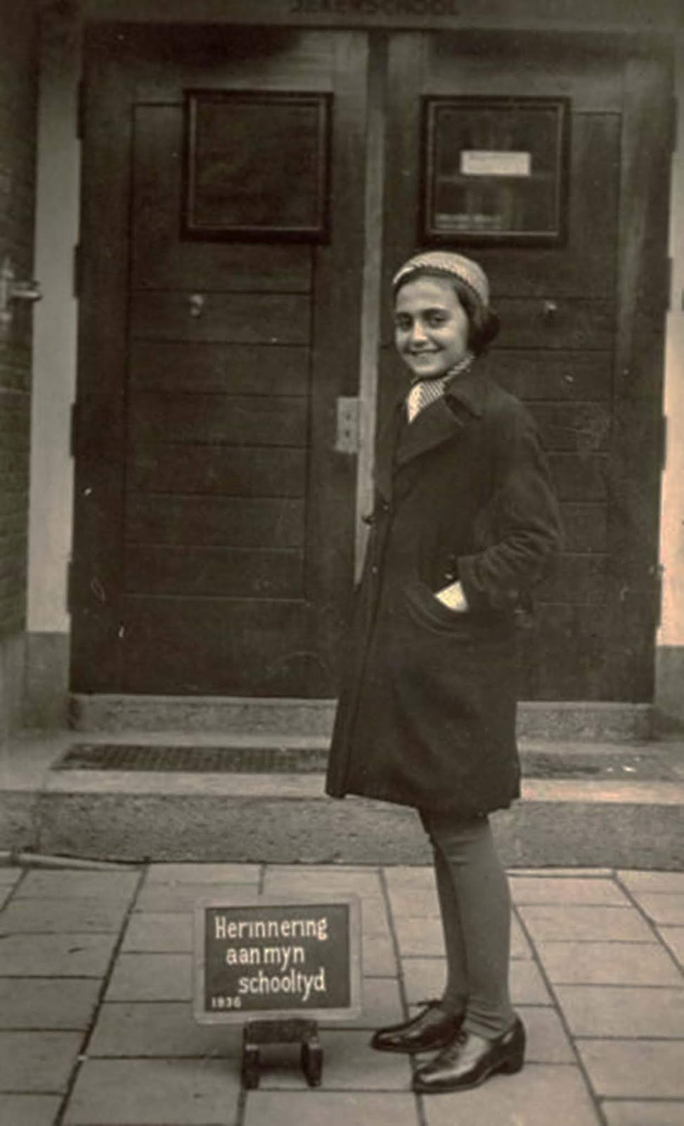 Margot Frank, the older sister of Anne Frank, standing in front of the doorway of the Jeker school in Amsterdam with a plaque at her feet that says 'memory of my school year 1936' in Dutch.