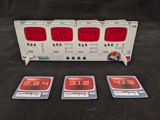 The display stand. Four cards have been slotted into the red cellophane windows, revealing the words 'scream,' 'ink,' 'window,' and 'white.' In front of it are three of the floppy disk cards, turned face up to reveal the number codes '2.3.4,' '3.1.2,' and '4.1.3.'
