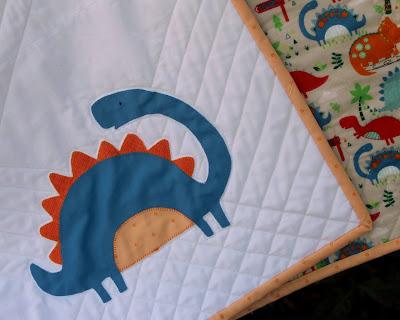 blue dinosaur appliqued baby quilt block with blanket stitching