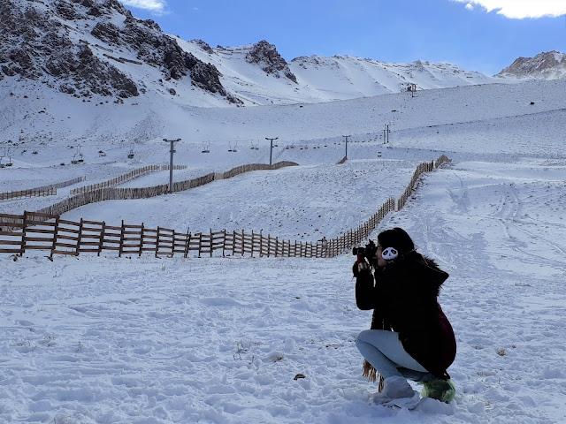 mulher fotografando  uma paisagem