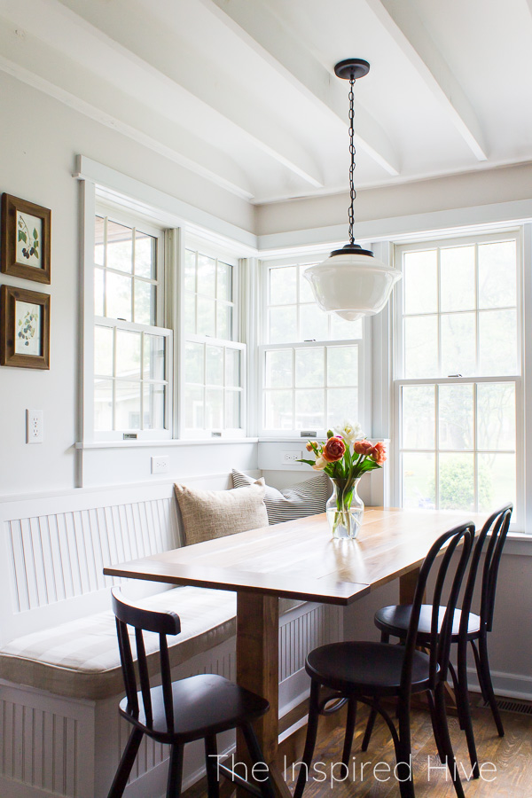 Breakfast nook with banquette bench seating, farmhouse table, and schoolhouse light
