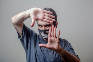 Man in gray t-shirt picture-framing his face with his hands