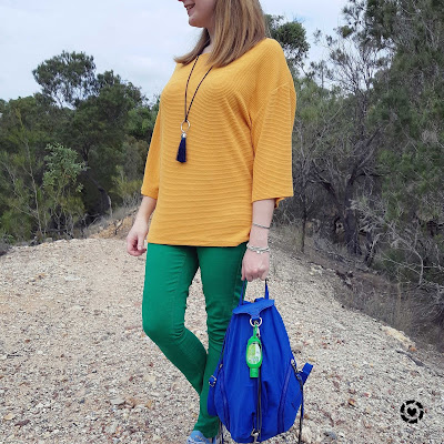 awayfromtheblue Instagram | Kmart short sleeve textured dolman top in marigold with green skinny jeans and bright blue backpack