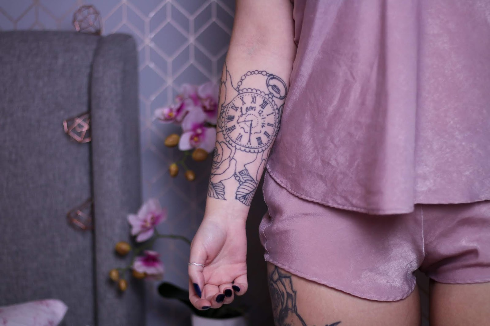 Mid shot photo of Jordanne standing in bedroom with a grey bed, pink orchid and white bedside table out of focus in the background. Jordanne is wearing pink silk pyjamas with her half sleeve tattoo on display facing the camera. The tattoo is a pocket watch with roses around it in black and white.