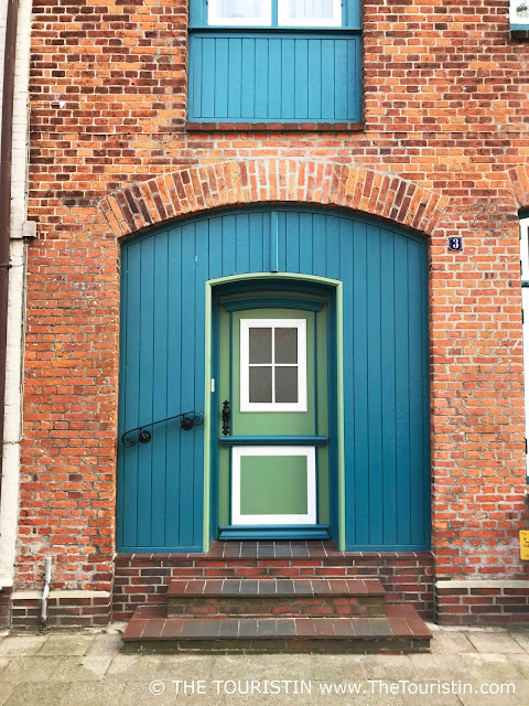 A red brick facade with a wooden door and shutters painted in light green and teal
