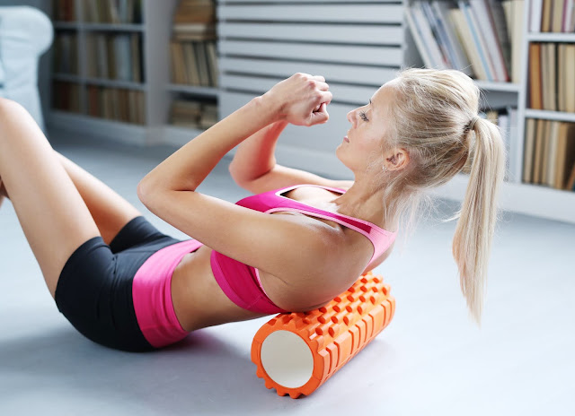 women working out back muscles with a foam roller