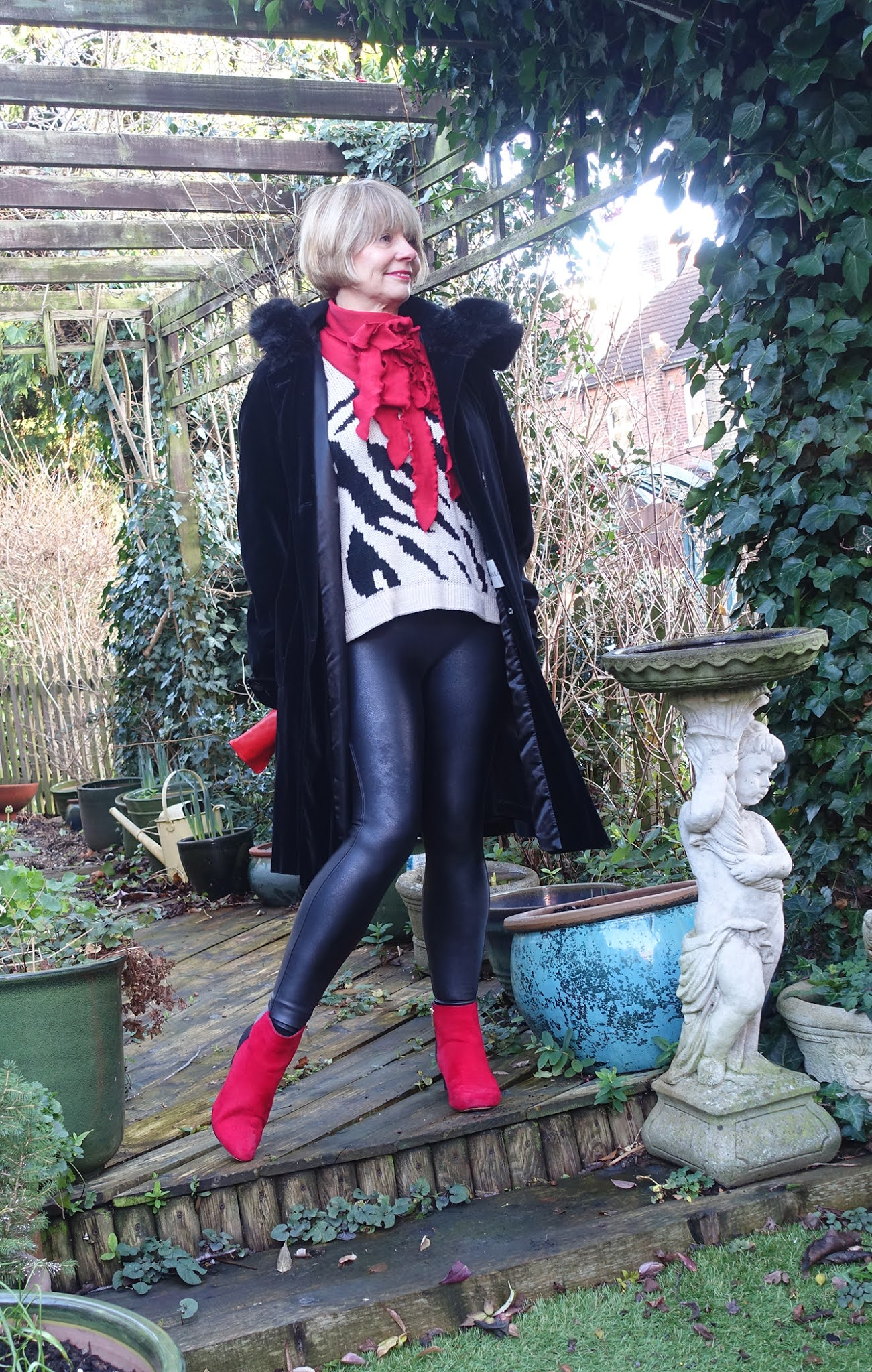 Is This Mutton blogger Gail Hanlon in black hooded velvet coat and faux leather leggings with red Rew scarf, red and black boots and red gloves for the latest challenge Out and About
